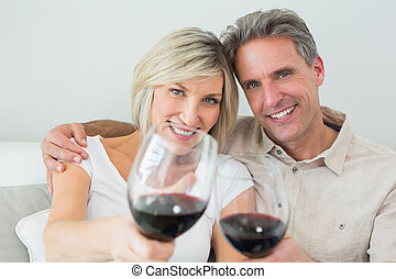 Couple holding out wine glasses at home
