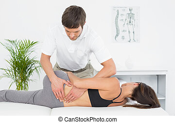 Male physiotherapist massaging woman's back in the medical...