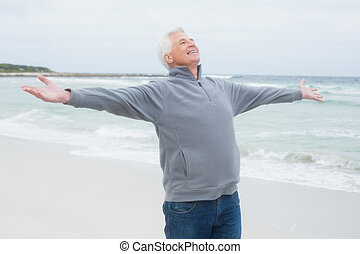 Senior man with arms outstretched at beach - Casual senior...