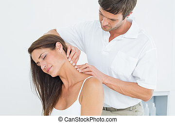 Male chiropractor massaging a young woman's neck in the...