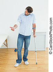 Young man with crutch and bandaged hand