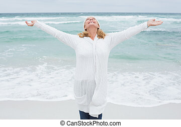 Senior woman with arms outstretched at beach - Casual senior...