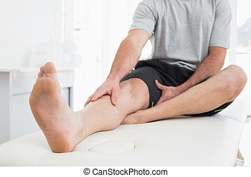 Low section of a man with hands on a painful leg - Low...