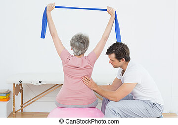 Senior woman on yoga ball with a physical therapist - Senior...
