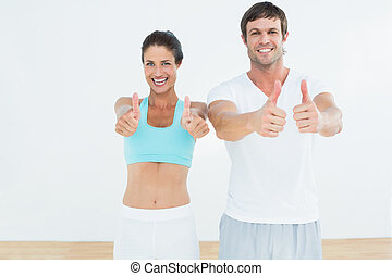 Happy fit couple gesturing thumbs up in fitness studio -...