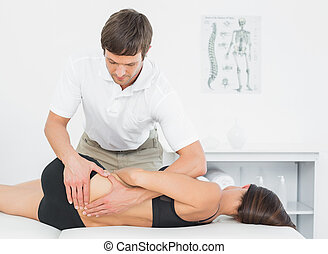 Physiotherapist massaging womans back in medical office -...