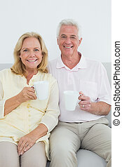 Senior couple with coffee cups at home