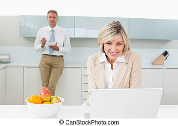 Woman using laptop and man in background at kitchen -...
