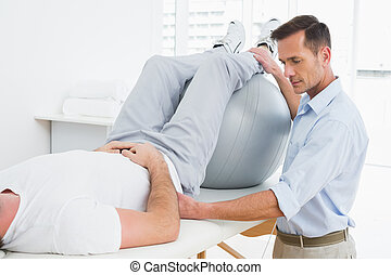 Physical therapist assisting man wi - Physical therapist...
