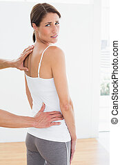 Physiotherapist examining woman's back in medical office -...