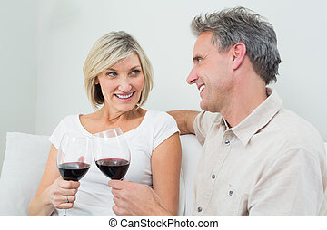 Couple toasting wine glasses at home - Relaxed happy couple...