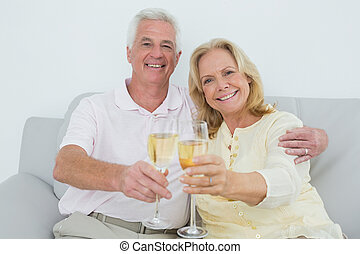 Senior couple toasting champagne flutes at home - Relaxed...