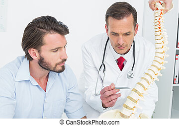 Male doctor explaining the spine to a patient in medical...