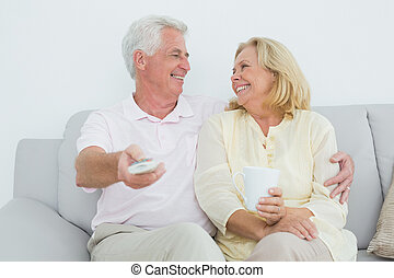 Cheerful senior couple watching tel - Relaxed cheerful...