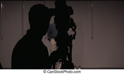 Studio shot of cameraman - Studio shot of young man with...