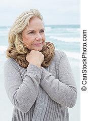 Senior woman looking away at beach - Contemplative casual...