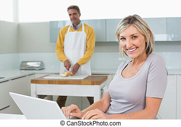 Woman using laptop and man chopping vegetables - Woman using...