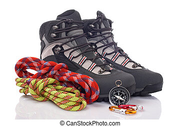 Climbing gear - Hiking boots, two rope and compass reflected...