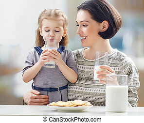 healthy food - girl drinking milk at the kitchen