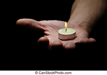 Hand carrying light - Candle on the mans hand on a black...