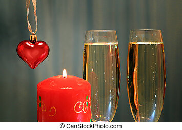 glasses with champagne with heart and candle