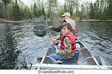 A young fisherman in a canoe smiles seeing walleye netted -...