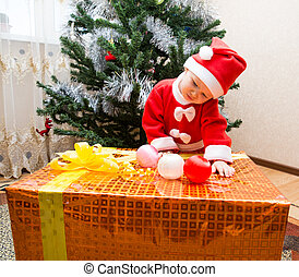 Santa baby girl  with gift box near Christmas tree at home