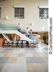 Medical Team And Patient Walking On Stairs - Side view of...