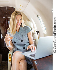Businesswoman Using Laptop In Private Jet - Happy...