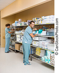 Nurses Arranging Stock On Shelves In Storage Room - Full...