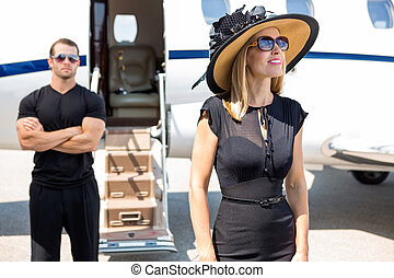 Happy Woman With Bodyguard And Private Jet In Background -...