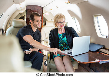 Business People Discussing Over Laptop On Private Jet -...