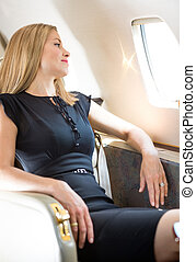 Rich Woman Looking Through Private Jets Window - Attractive...