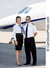 Airhostess And Pilot Standing Against Private Jet - Full...