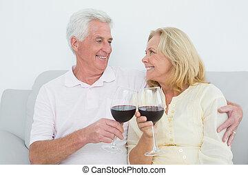Senior couple toasting wine glasses - Relaxed senior couple...