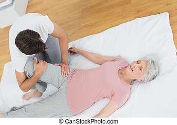 Physical therapist examining senior woman's leg