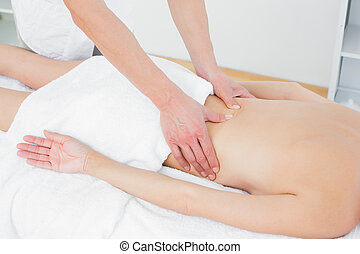 Mid section of a physiotherapist massaging womans back -...