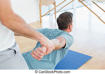 Therapist assisting man with stretching exercises