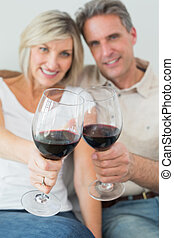Happy couple holding out wine glasses