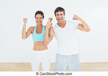 Cheerful fit couple clenching fists in fitness studio -...