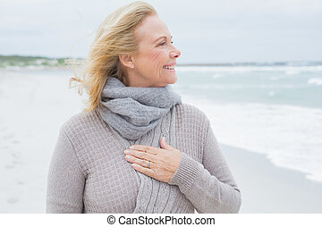 Happy senior woman looking away at beach - Happy...