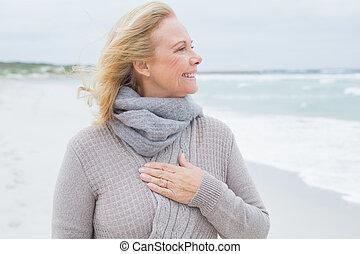 Happy senior woman looking away at beach - Happy...