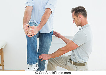 Therapist assisting young man with stretching exercises