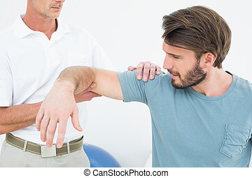 Male physiotherapist massaging a young mans arm in the...