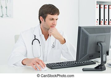 Doctor using computer at medical office - Concentrated male...