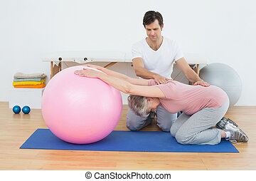 Physical therapist assisting senior woman with yoga ball -...