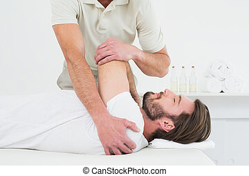 Male physiotherapist stretching a young mans hand in the...