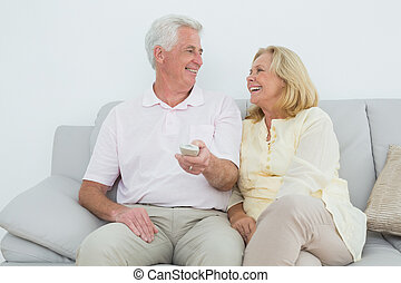 Cheerful senior couple watching television - Relaxed...