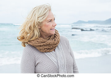 Contemplative senior woman looks away at beach -...