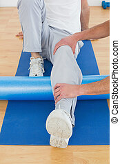 Physical therapist examining mans leg - Physical therapist...